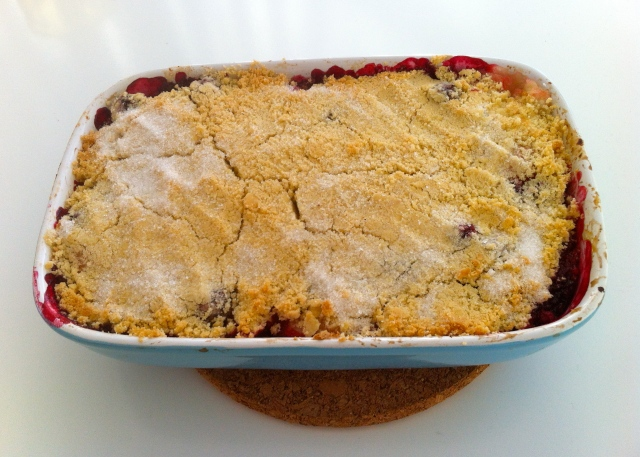 A dish filled with apple and blackberry crumble.